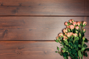 Spring layout with place for text. A bouquet of roses on a dark wooden background.