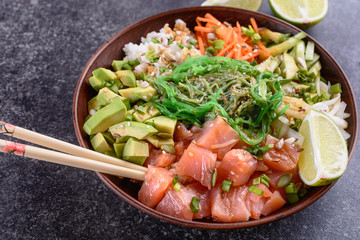Homemade healthy Poké bowl with rice, salmon, avocado, white onion, scallion greens, sesame oil, soy and sesame sauce, seaweed (wakame) and other ingredients are ready to eat