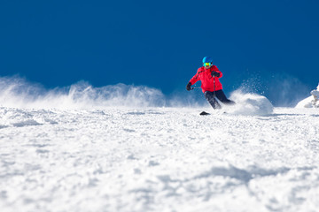 Wall Mural - Man skiing on the prepared slope with fresh new powder snow