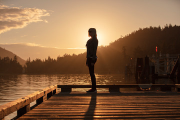a woman stands on a pier at sunset
