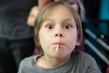 a boy sucks on a lollipop