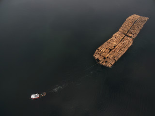 an aerial photo of a tug pulling logs
