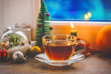 festive tea party. a cup of tea and a teapot. on the background of New Year and Christmas decorations. near the window with a blue, cold, winter background.