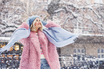 Outdoor portrait of young beautiful fashionable happy smiling girl wearing trendy pink faux fur winter coat, light blue beanie hat, scarf, posing in snow covered street. Copy, empty space for text Fotomurales