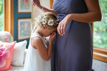 A flower girl hugs her mom