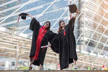 Two girls jumping Glad to graduate