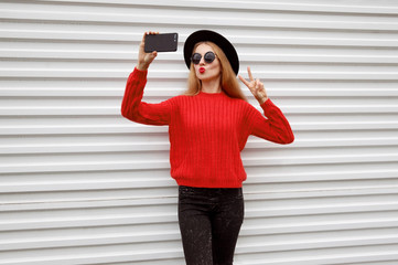 Fashionable young woman blowing red lips sends sweet air kiss taking selfie picture by phone in knitted sweater on white wall background