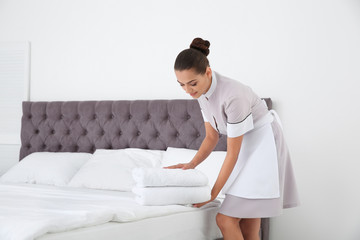Young chambermaid putting clean towels on bed in hotel room