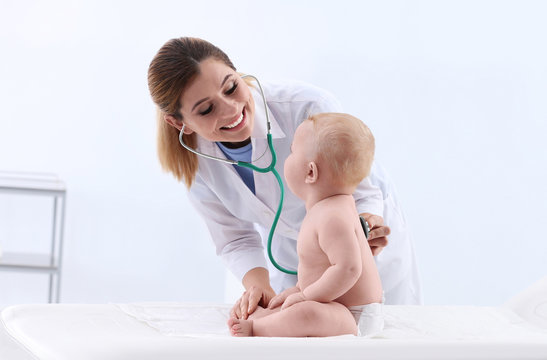 Children's doctor examining baby with stethoscope in hospital. Space for text