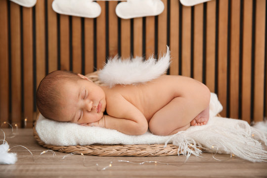 Cute newborn baby as Christmas angel in decorated studio