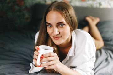 Attractive smiling european woman using laptop and drinking coffee while lying on her bed. Young woman drinking coffee at home, start, concept in the morning, early in the morning. Stylish Toned