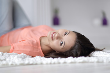 close up. young woman lying on white carpet in living room and looking at camera