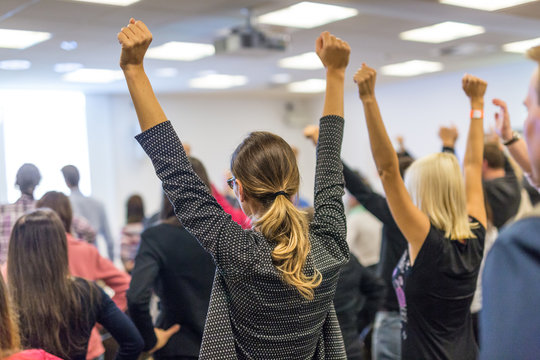 Life coaching symposium. Speaker giving interactive motivational speech at business workshop. Rear view of unrecognizable participants feeling empowered and motivated, hands raised high in air.