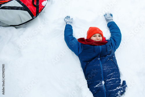 98b23743a cute young boy in hat blue jacket holds and plays with snow