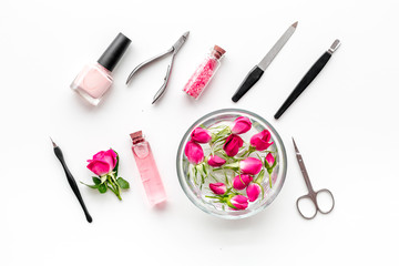 manicure equipment with nail polish and rose petals white background top view