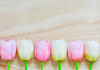 pink and white artificial tulips on wood background, copy space