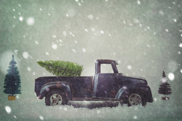 Scene of an antique vintage toy truck carrying a bottle brush Christmas tree home in the snow