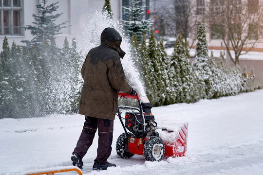 Man working with snow blowing machine. Remove snow from parking places, clearing driveway after winter storm in the city. Worker using snow throwing machine on winter day