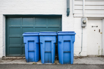 Three blue trash cans with wheels by a garage door in an alley
