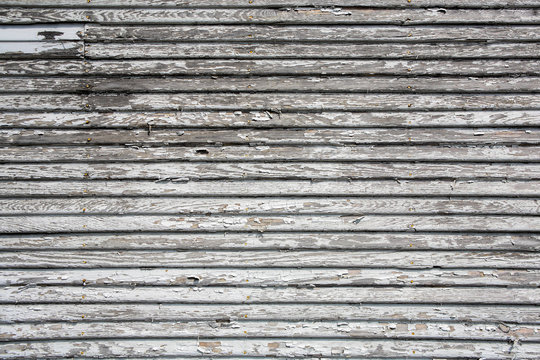 Weathered wooden lap siding with peeling paint