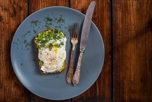 Toast with avocado and poached egg on round gray plate blackboard. Copy space Top view.