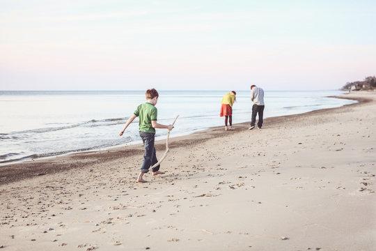 Boy walking down the beach with a walking stick