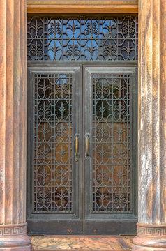 Ornate iron door framed by vertical fluted columns