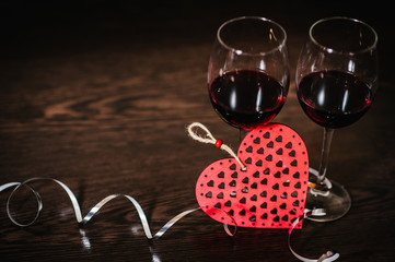 A romantic love concept holiday, ribbons, wine, red hearts on brown wooden background. Place for text. concept Women's Day, eighth of March. Wedding, jubilee. St. Valentine's Day.