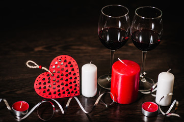 A romantic love concept holiday, candles, ribbons, wine, red hearts on brown wooden background. Place for text. concept Women's Day, eighth of March. Wedding, jubilee. St. Valentine's Day.