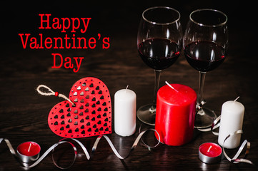 Text happy Valentine's Day. A romantic love concept holiday, candles, ribbons, glasses of wine, red hearts on brown wooden background. Place for text.