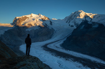 Man looking at the Monta Rosa massif from the Gornergrat in Switzerland.
