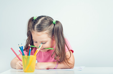 beautiful cute little girl holding pencil in mouth and drawing picture on white paper