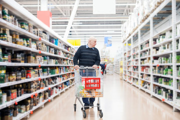 Aged man with   trolley buying groceries in   store