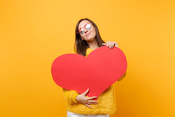 Tender pretty young woman in fur sweater, heart glasses holding, hugging with empty blank red heart isolated on bright yellow background. People sincere emotions, lifestyle concept. Advertising area.
