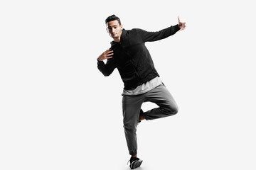 Stylish young man wearing a black sweatshirt and gray pants is dancing street dances on a white background
