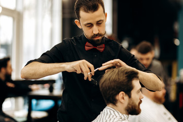 Сharismatic barber with mustache dressed in a black shirt with a red bow tie scissors the hair of a young man in a barbershop