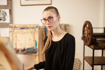 Charming fair-haired girl in glasses dressed in black blouse sits at the easel and paints a picture in the art studio