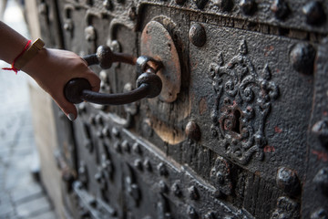 Black wooden door architecture of an ancient building is seen in this closeup. A hand is seen pulling the metal big knob of the door to open it.
