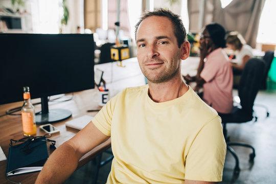 Portrait of confident businessman sitting in creative office