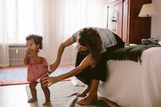 Mother adjusting daughter's diaper at home