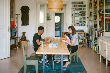 Young man using laptop while woman playing with daughter at dining table in house