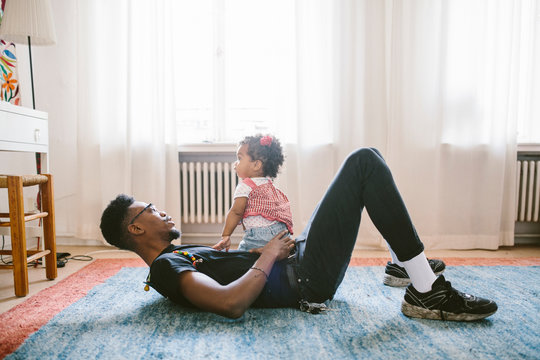 Side view of father and daughter playing at home