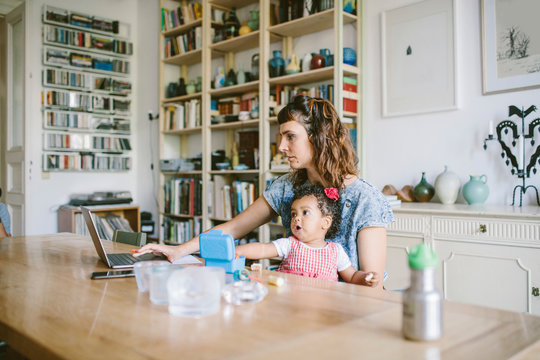 Mother using laptop while sitting with daughter at home
