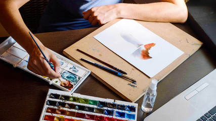 Young woman passes a lesson in watercolor painting online at home