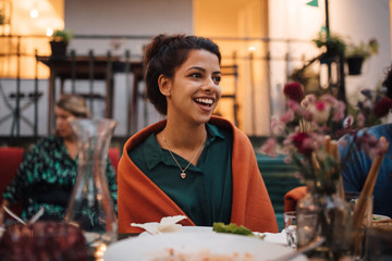 Smiling young woman looking away while sitting at table during dinner party
