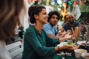 Smiling woman gesturing during party in backyard