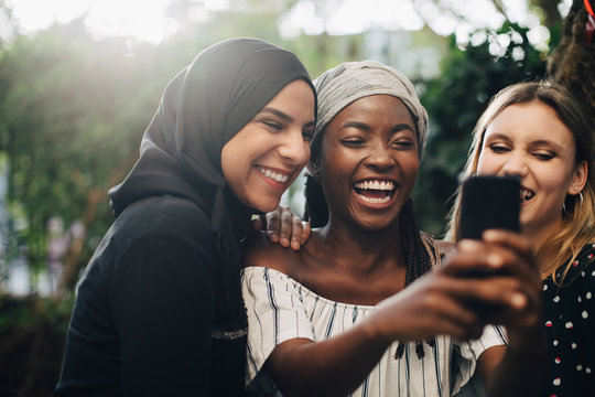 Smiling friends taking selfie through smartphone in backyard