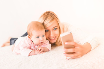 Beautiful blond mom and her daughter baby make selfie on mobile phone.