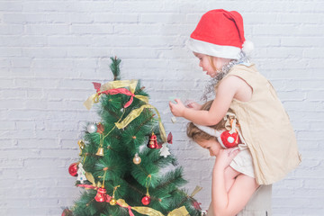 girl, child decorates Christmas tree on white brick wall background