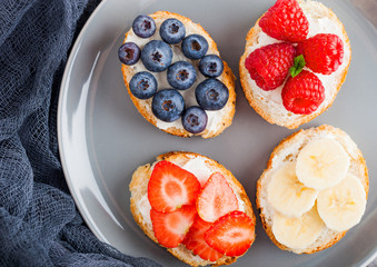Fresh healthy mini sandwiches with cream cheese, fruits and berries in grey plate with cloth. Strawberries, blueberries, bananas and raspberries on stone kitchen table background.Top view.